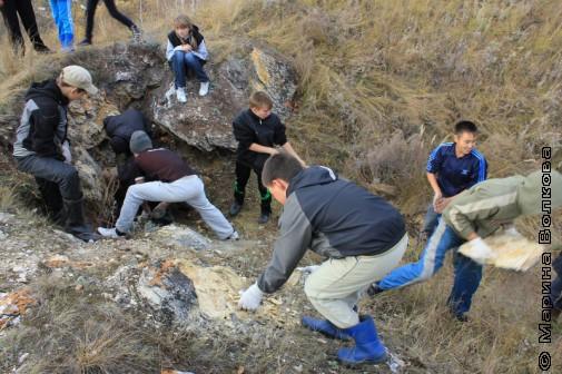 Школьники убирают камни от входа в пещеру