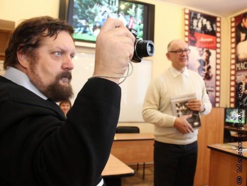 Краевед Владимир Боже фотографирует на презентации