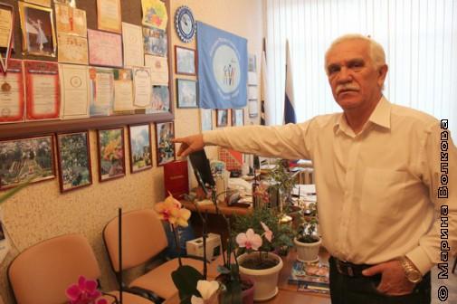Дипломы и фотографии цветов висят рядом