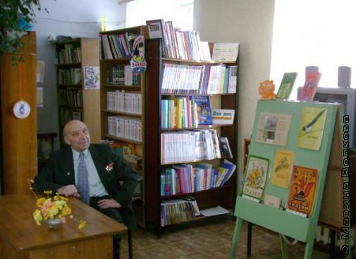 Г. Е. Осетров рядом с выставкой книг Л.И.Куликова