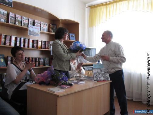 Поэт Александр Петров вручает цветы гостям