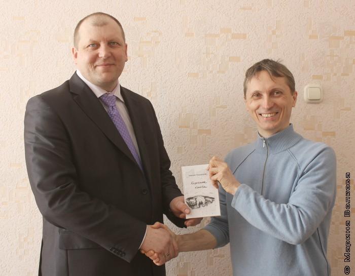 Михаил Придворов дарит Алексею Паташенко книгу для школьной библиотеки
