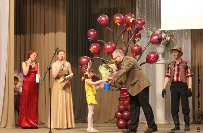 А дети поздравляю Константина Сергеевича: цветы и лейка для выращивания талантов