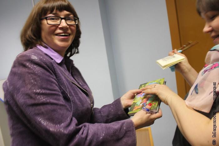 Елена Соловьева передает книгу с автографом читательнице