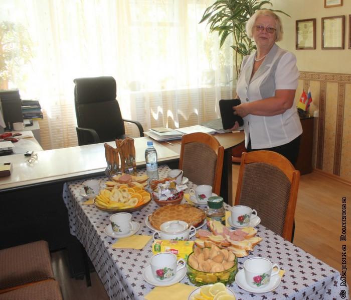 Наталья Шмидт у стола с угощением
