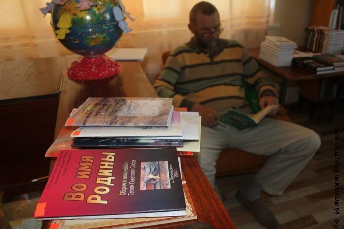 Сергей Поляков изучает книги кизильских авторов