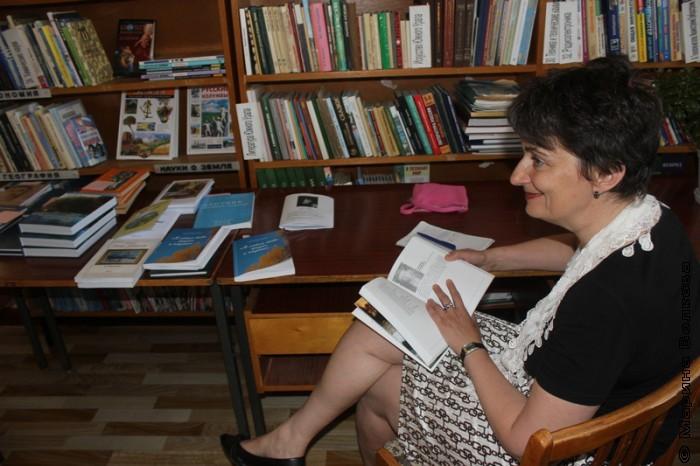 Ирина Аргутина изучает книги, изданные в Кизильском