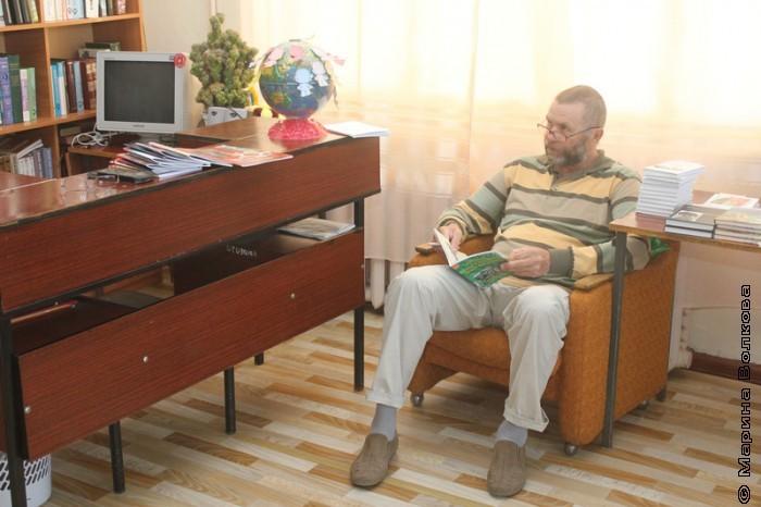 Сергей Поляков изучает книги, изданные в Кизильском