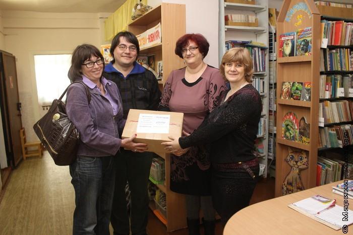 Елена Соловьева передает коробку со своими книгам библиотекарям Копейска