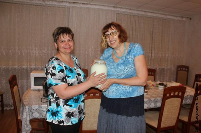 Вера Кугенева передает парное молоко Марине Волковой
