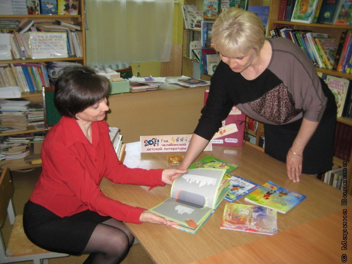 учителя смотрят книги из чемоданчика